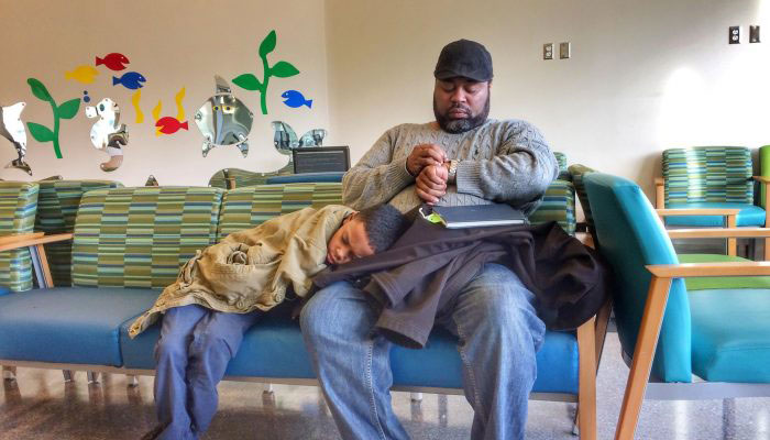 A father sits in a hospital waiting room with his young son resting on his lap.